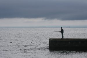 Man fishing ont he beach off a pier