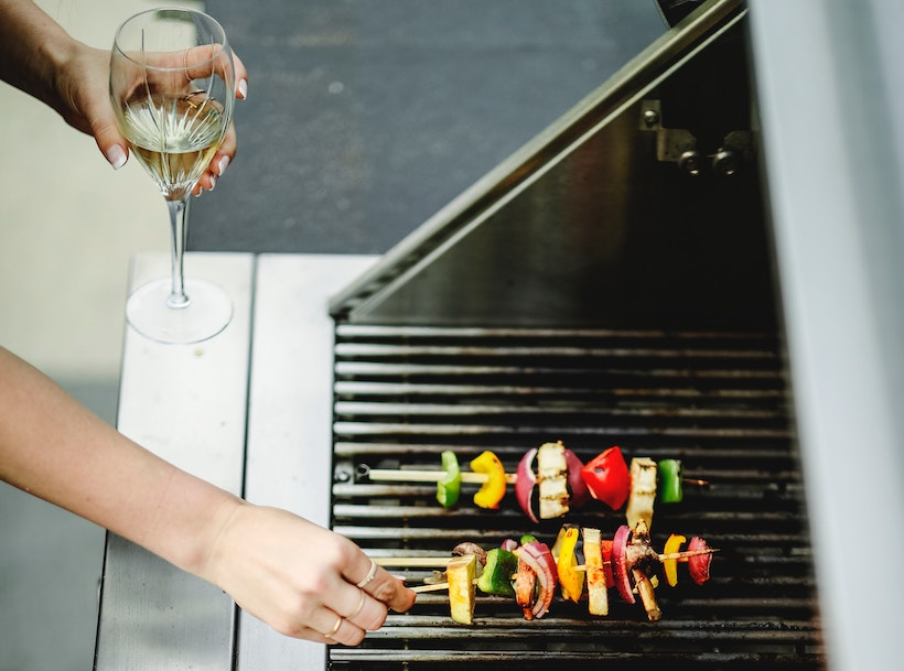 Woman grills kabobs with wine in hand