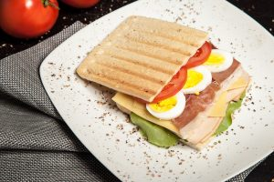 Deli meat sandwich with eggs and tomato