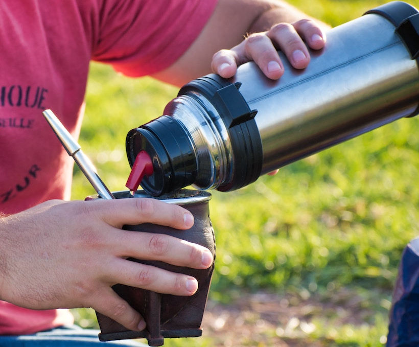 Man holding mug and pouring thermos