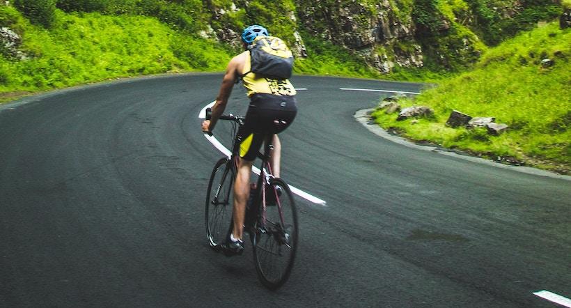 Man biking on left side of road around corner