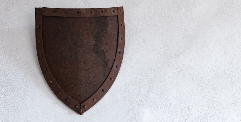 Rusted iron shield hanging on a wall
