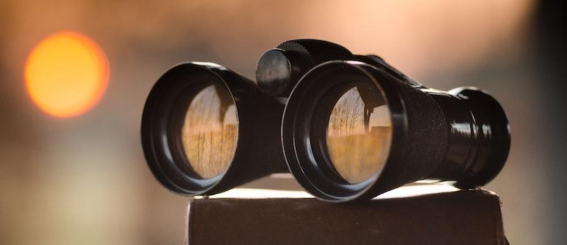 Black binoculars with sun in background