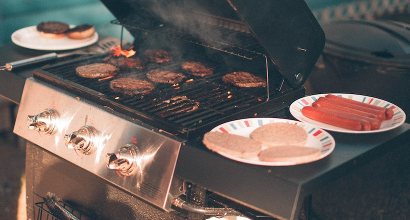 Burgers on the grill plus other foods ready to grill