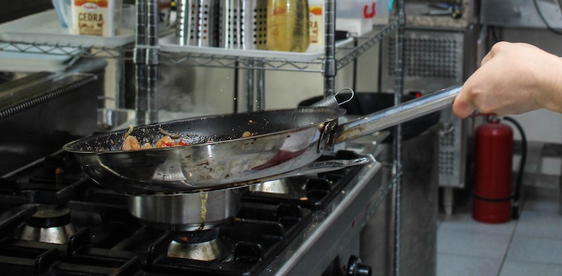 Stainless steel frying pan and a man's hand in a commercial kitchen