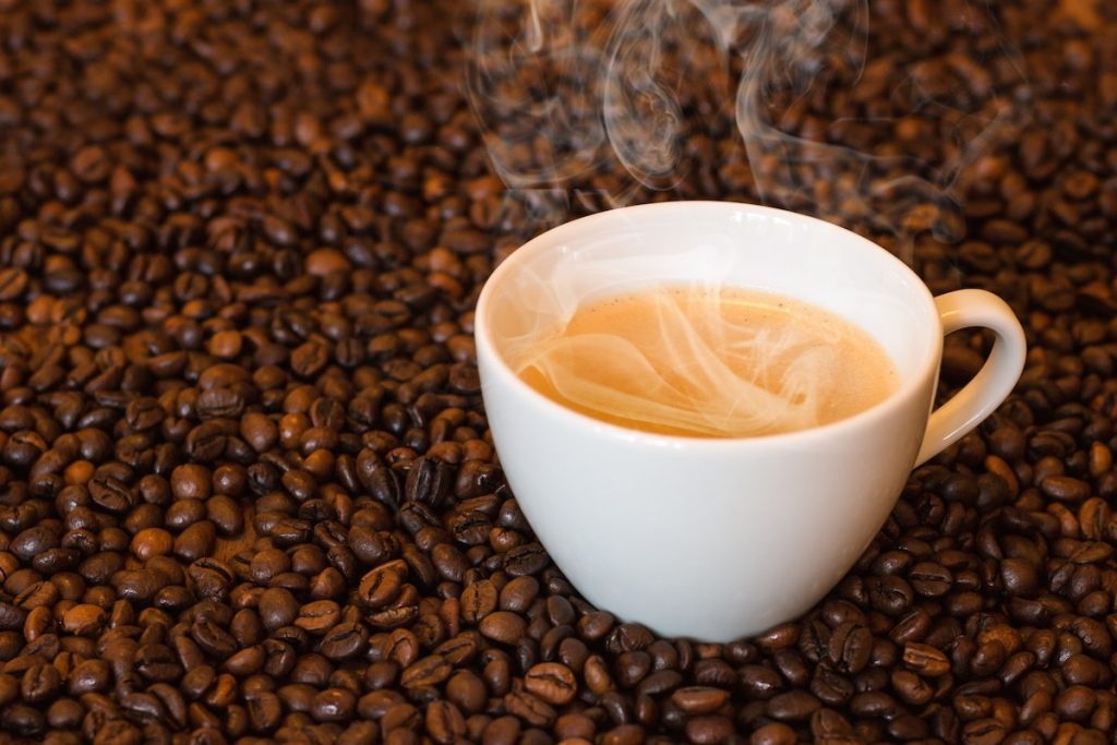 Coffee beans with cup and steam rising