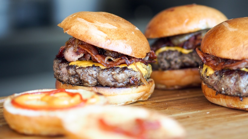 Four bacon cheeseburgers with perfectly placed buns