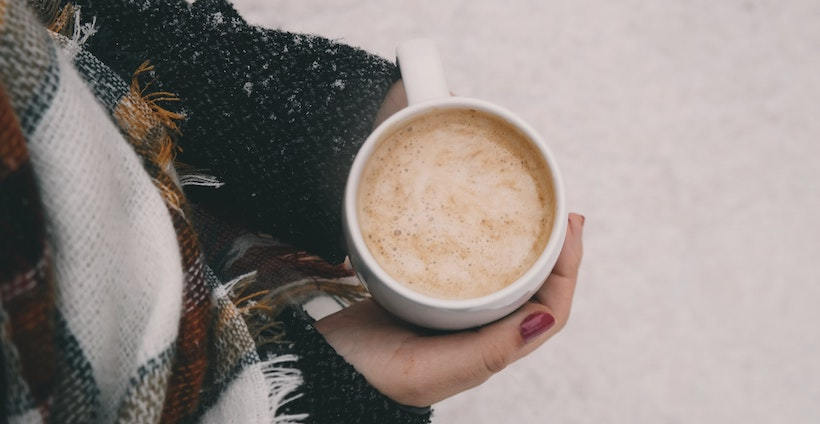 Lady in winter clothes holds a hot coffee