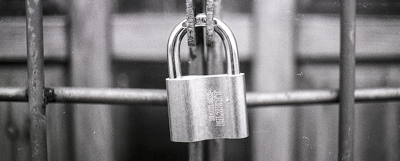 Padlock closed and protecting a gate