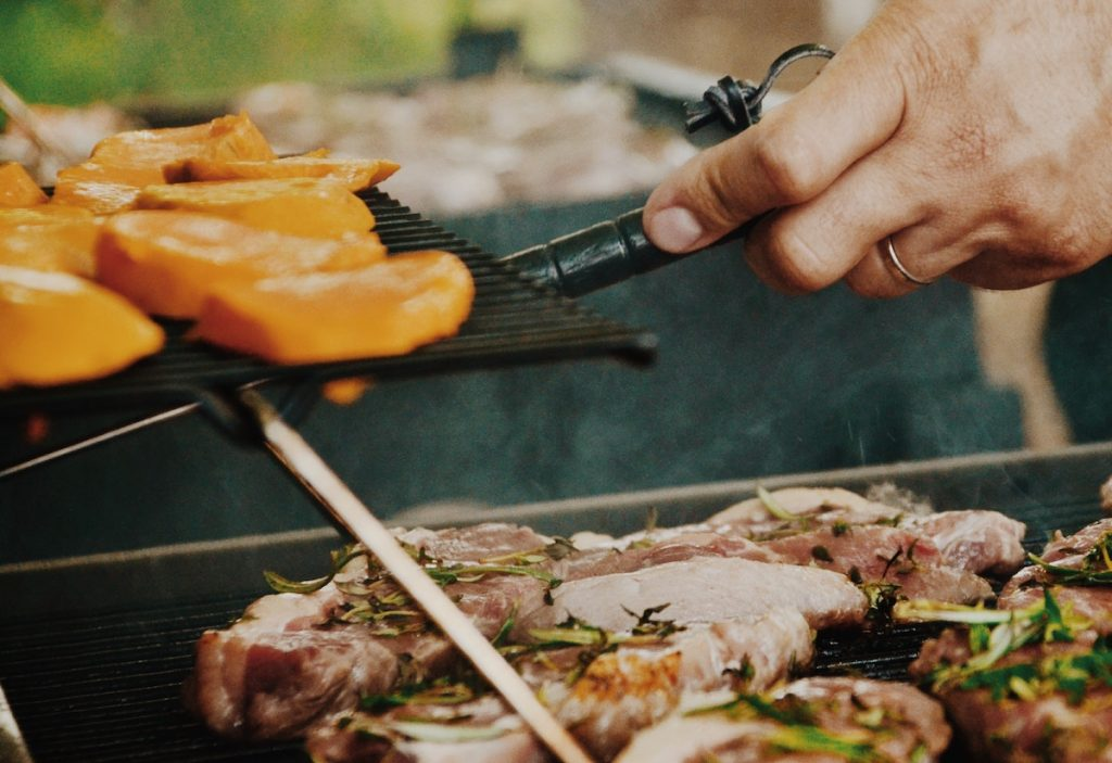 A man grills chicken loaded with herbs and veggies