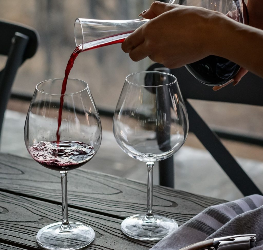 Person pouring red wine into two glasses