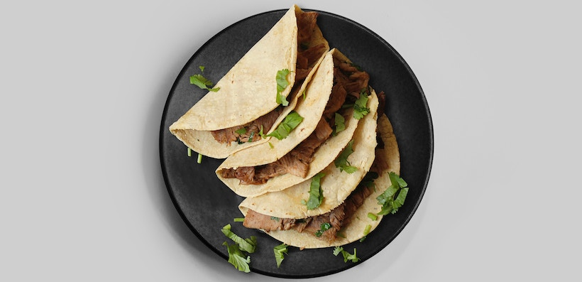 Tacos on a plate with cilantro and steak