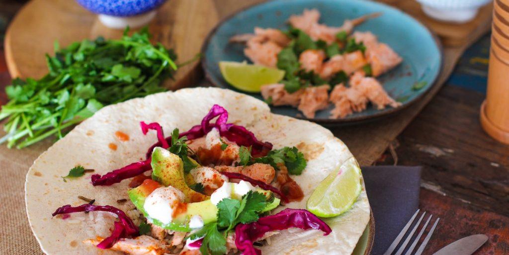 Shrimp, sauce, avocado, and lime on a soft taco