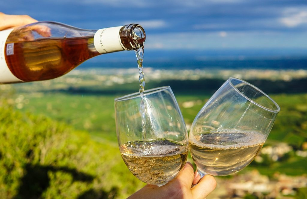 Pouring white wine into two glasses with a good view in background of fields