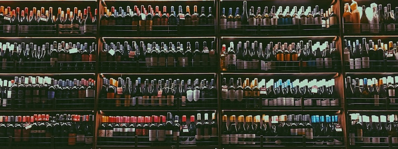 Many mostly red wines on a shelf