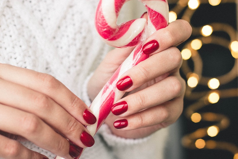 Lady holds giant candy cane and has bright red matching manicure