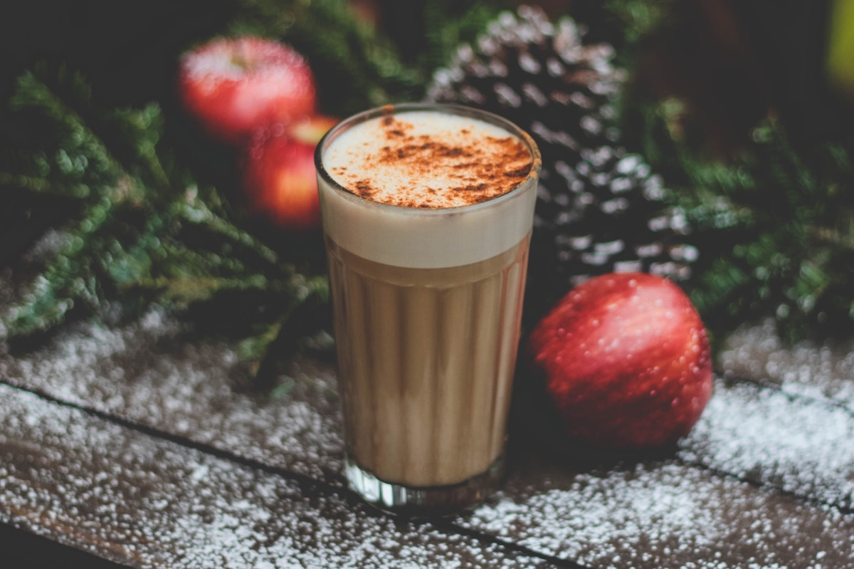 Eggnog with spices in a cup near Christmas decorations