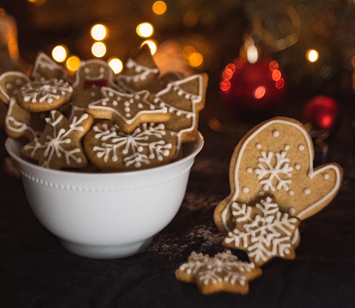 Gingerbread cookies in bowl with fire and lights in back