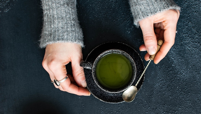 Lady mixing green tea in a cup