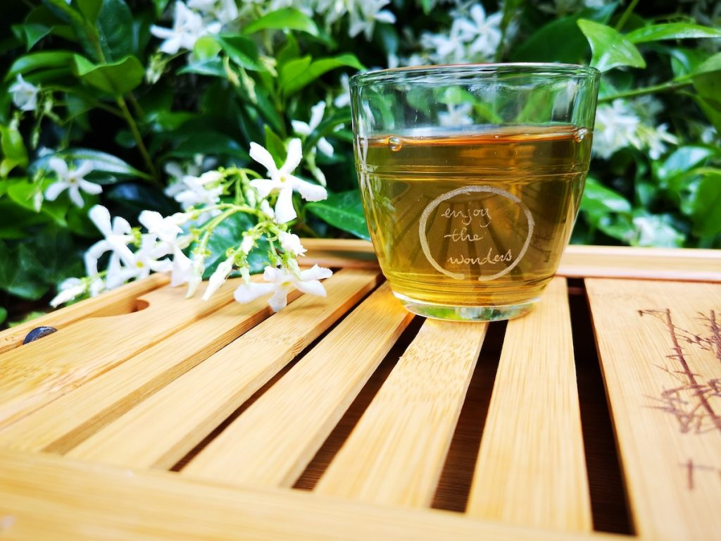 Clear jar on wooden table with green tea