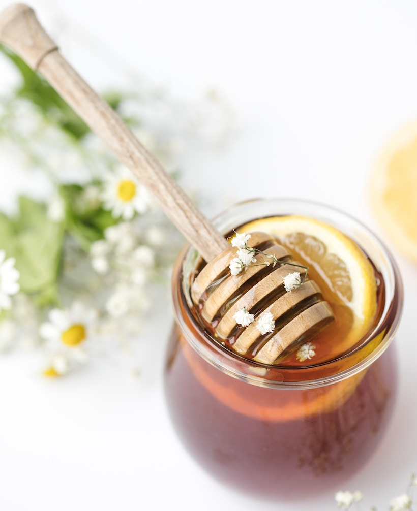 Honey and applicator inside a clear jar, with clover