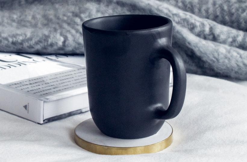 Ceramic mug next to a book