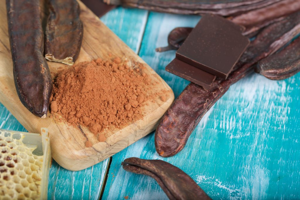 Carob pods and powder on a wooden surface with a cutting board