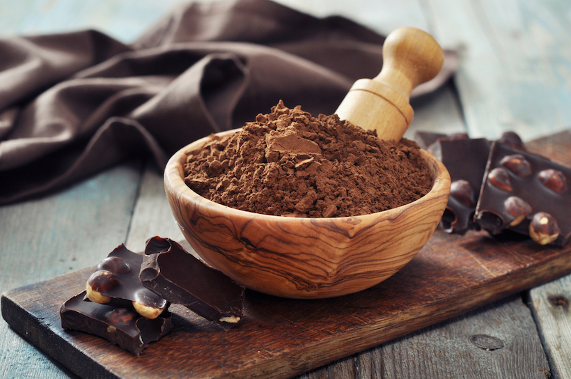Carob powder in bowl with carob pieces on wooden board