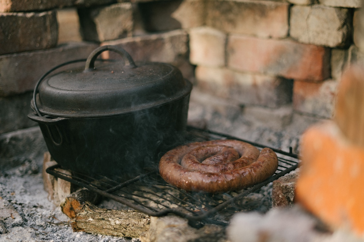 Boerewors cooked open flame next to a dutch oven