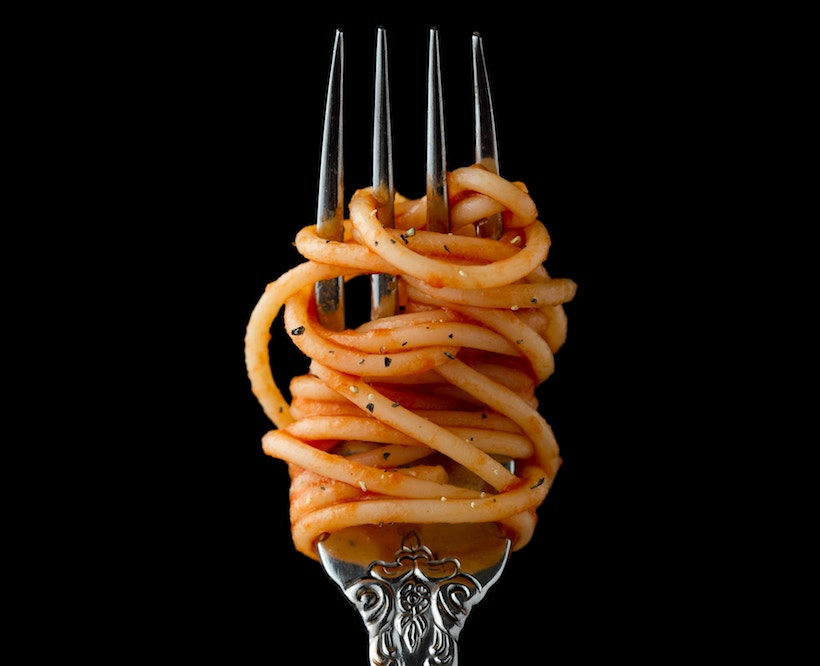 Spaghetti on a fork with sauce and herbs