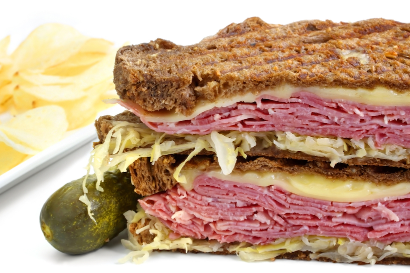 Reuben sandwich, with pastrami, sauerkraut, melting Swiss cheese on dark rye bread.  With dill pickle and potato crisps.