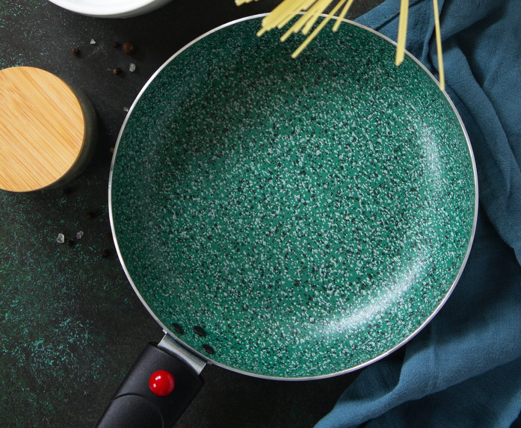 Empty ceramic frying pan with pasta stalks above