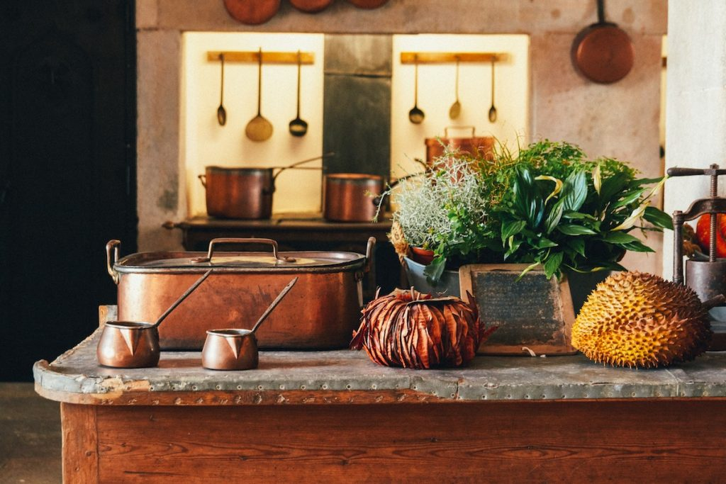 Copper baking pan and cups with plants in a kitchen
