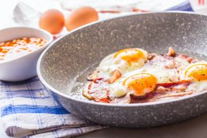 Ceramic pan cooking eggs and ham next to beans