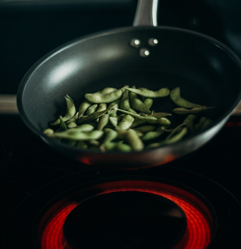 Green beans in a pan over a halogen burner
