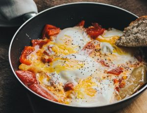 Non-stick pan with eggs and meat cooking inside