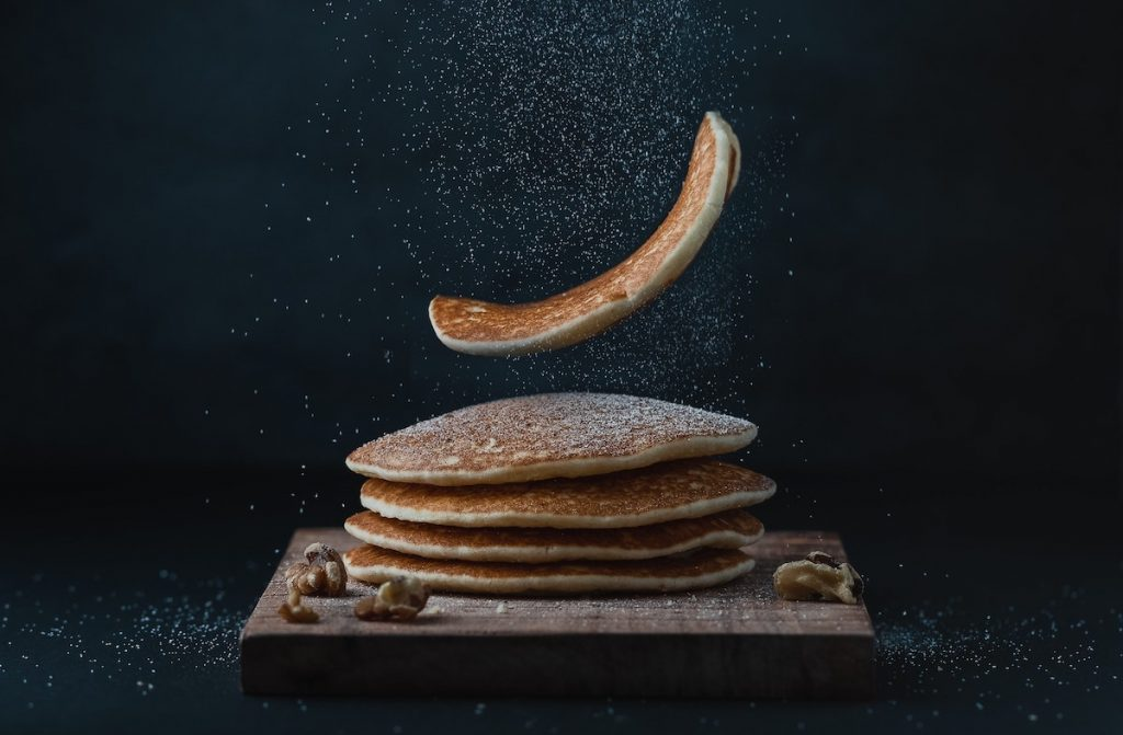 Sugar in air falling on a falling pancake with a stack below