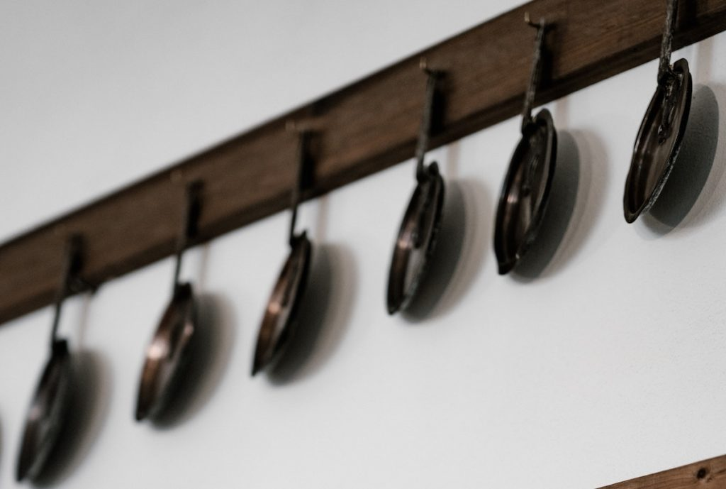 Black pans hanging on hooks on a wall