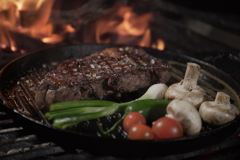Steak, veggies, and mushrooms on a grill pan