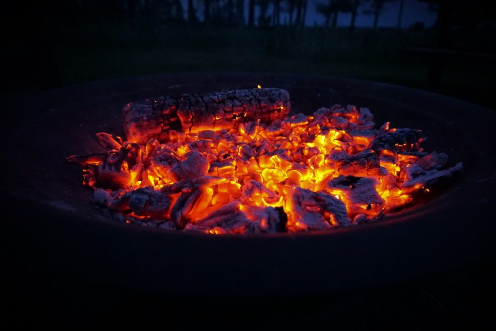 Burning charcoal in a firepit at night