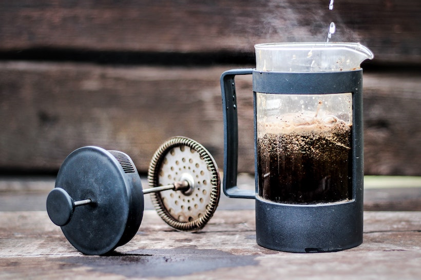 French press with coffee inside and deconstructed