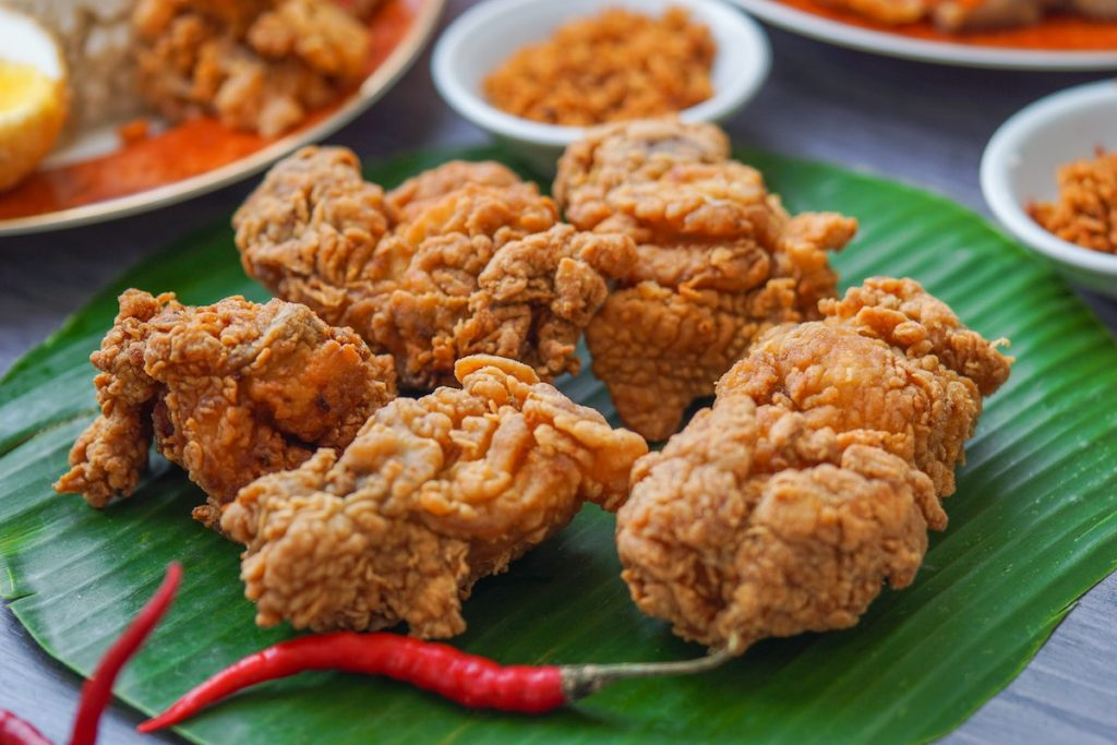 Fried chicken on a plate next to chili pepper