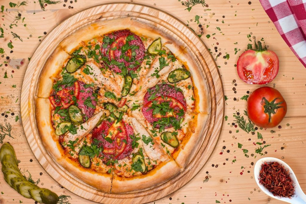 Pizza on a tray on a table with raw veggies surrounding