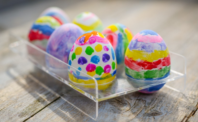 Assorted decorated Easter eggs in a plastic tray