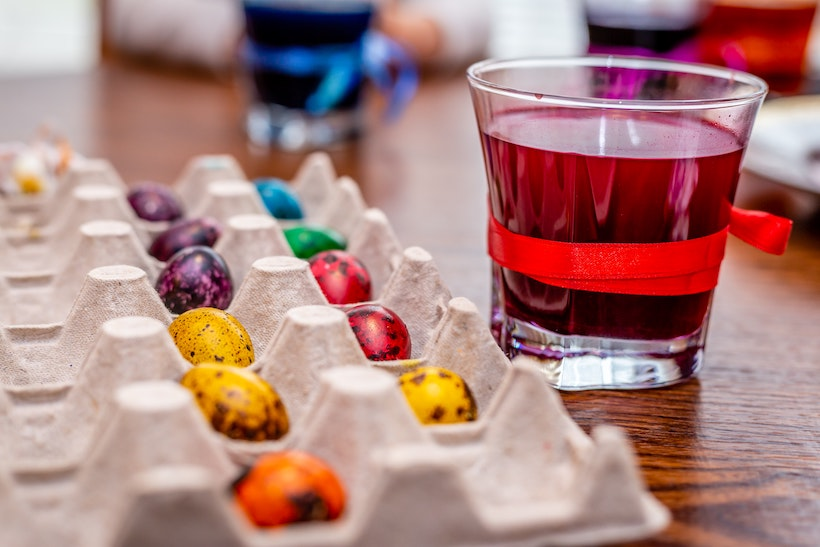 Easter eggs in a tray drying next to red dye water