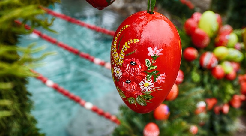 A red Easter egg on a tree with flowers