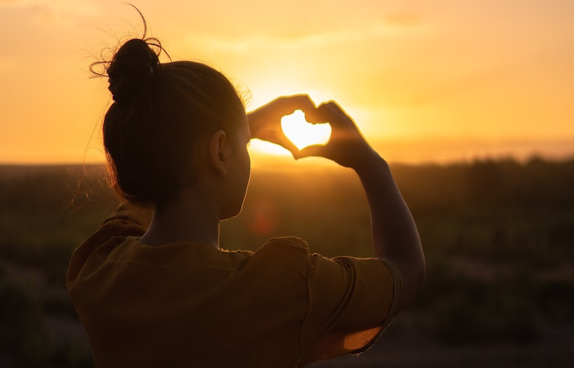 A woman captures the setting sun in her hands shaped like a heart