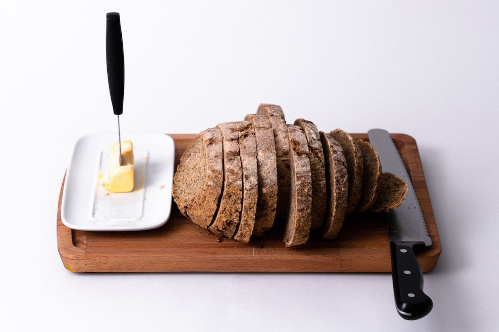 Serrated knife with sliced bread on cutting board plus butter