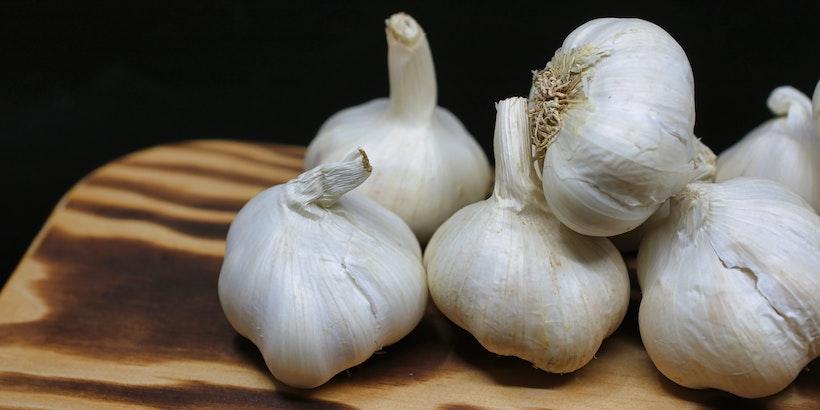 Garlic bulbs on a wood cutting baord