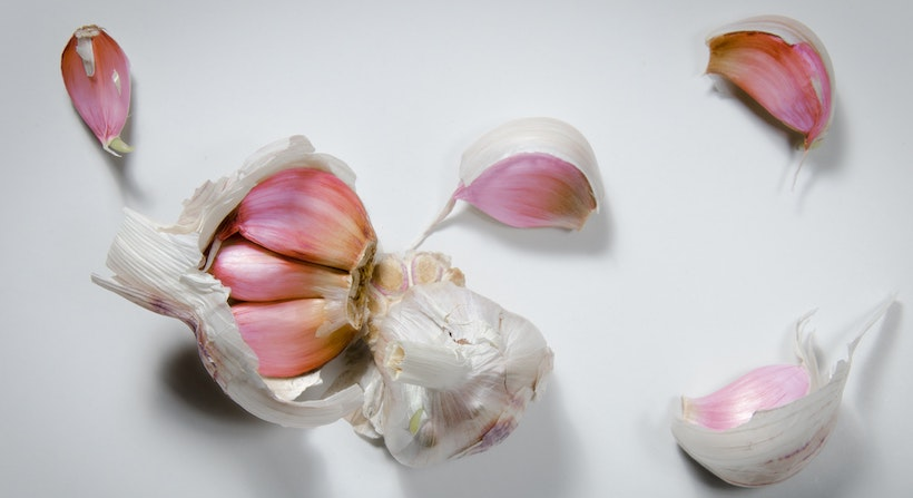 Cracked garlic showing outside and cloves